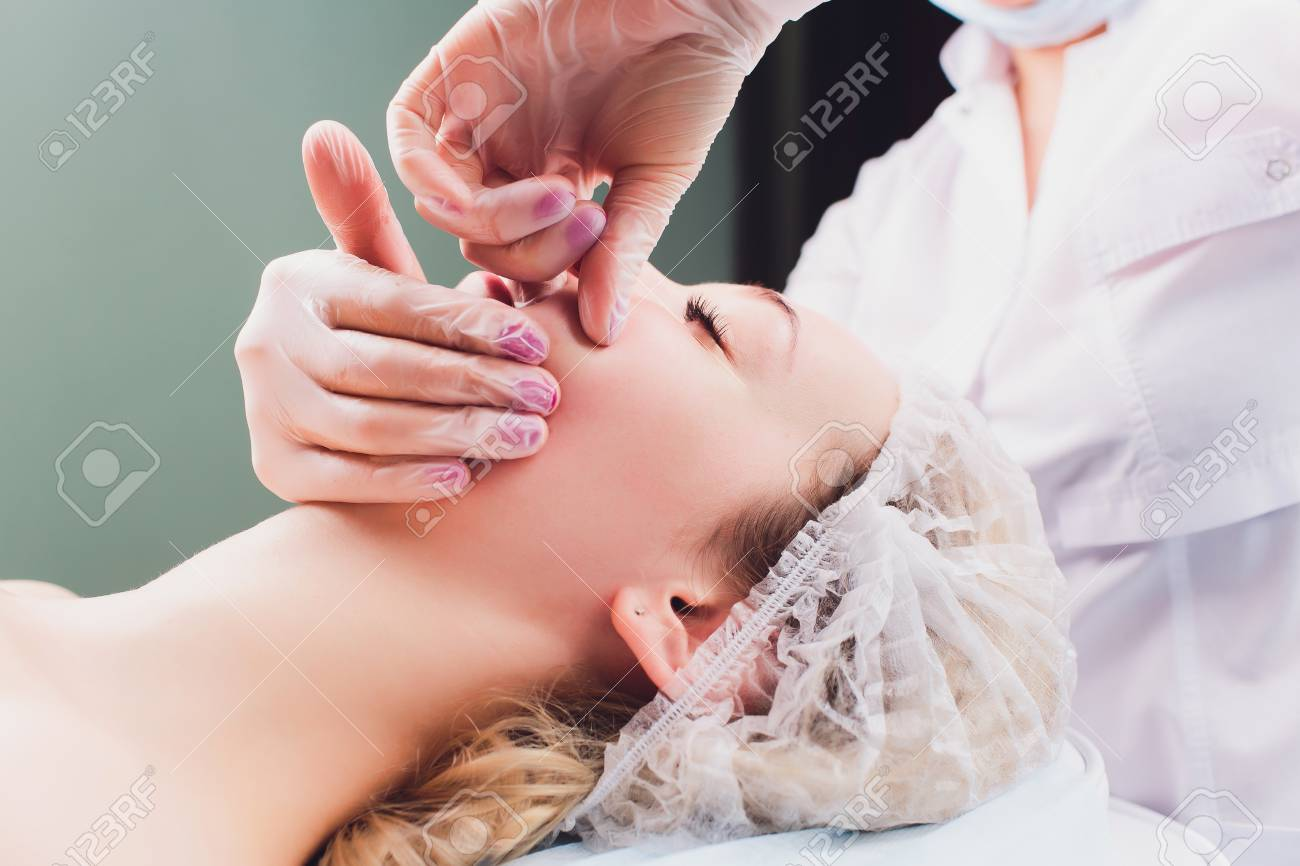 cosmetologist makes a buccal massage of the patients facial muscles. - 120897867