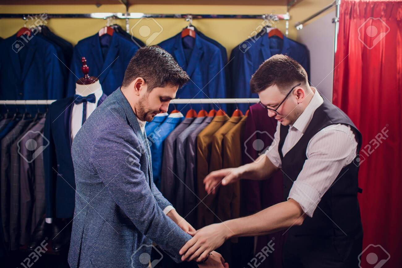 Businessman in classic vest against row suits in shop. Man helps another try on suit in clothing store - 121333141