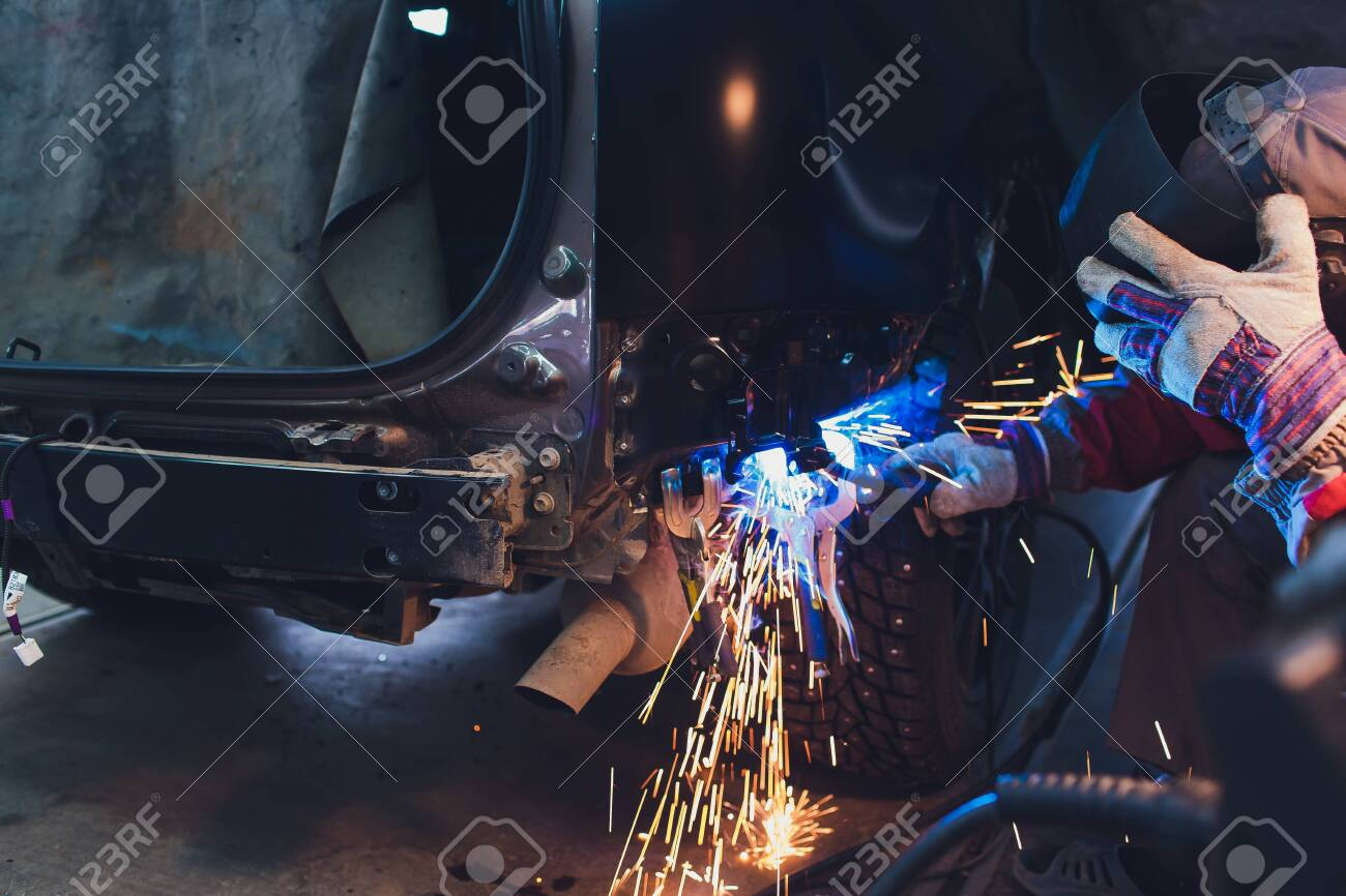 professional repairman worker in automotive industry welding metal body car with sparks - 121902984