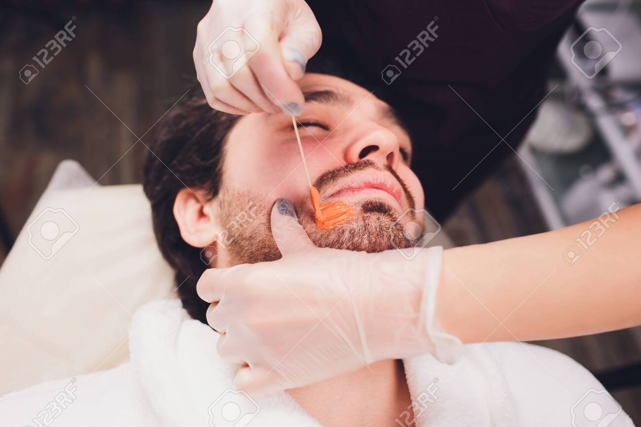 Hair removal. Mans face sugaring epilations beard trimming, yellow color, in cosmetology on the couch. - 121902196