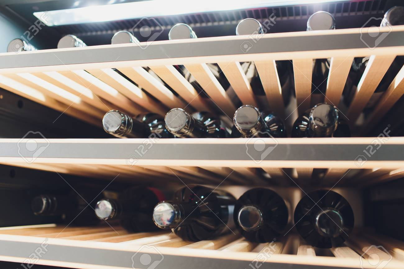 Storing bottles of wine in fridge. Alcoholic card in restaurant. Cooling and preserving wine. - 121702999