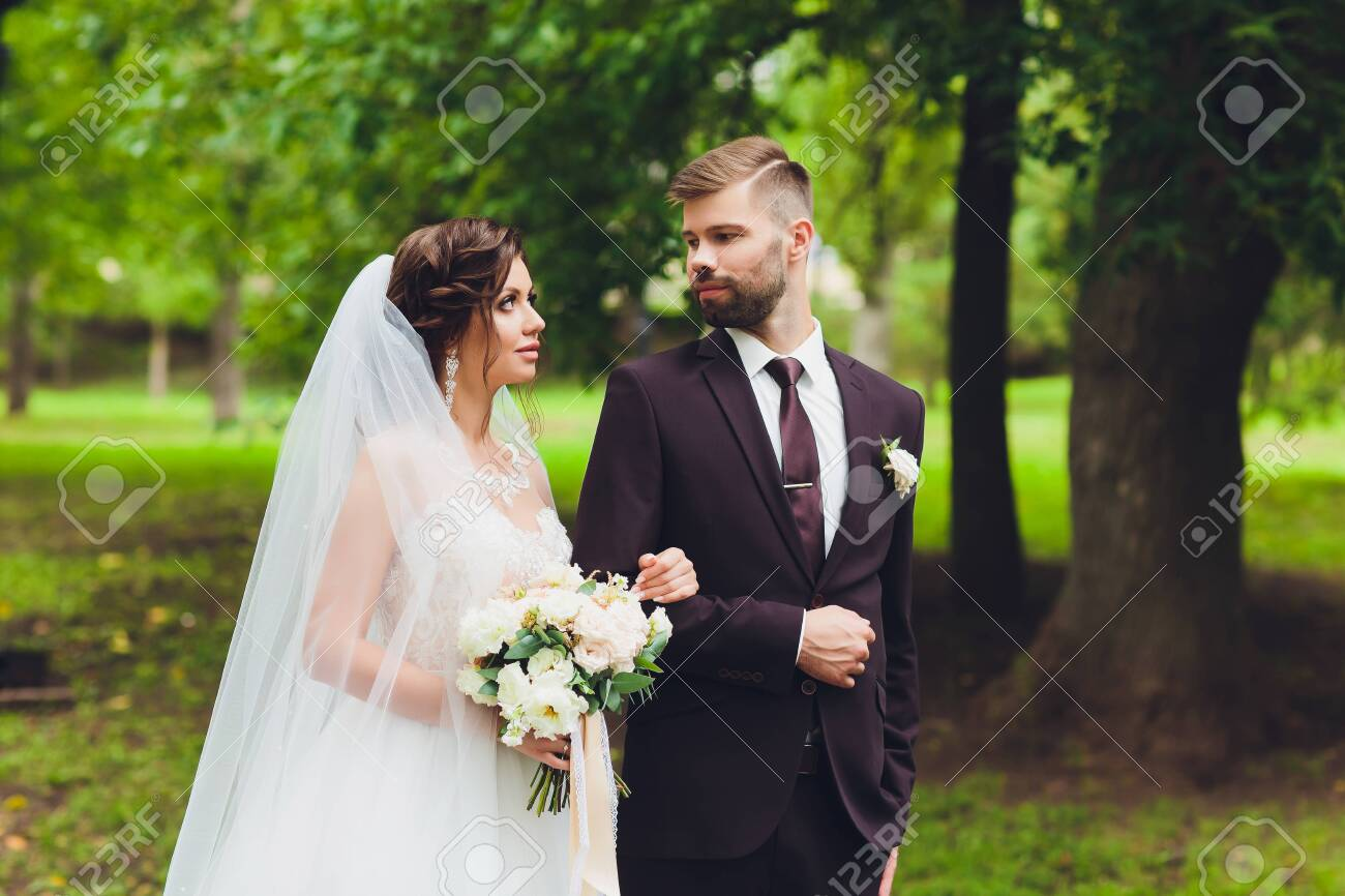 happy bride and groom at a park on their wedding day. - 137476533