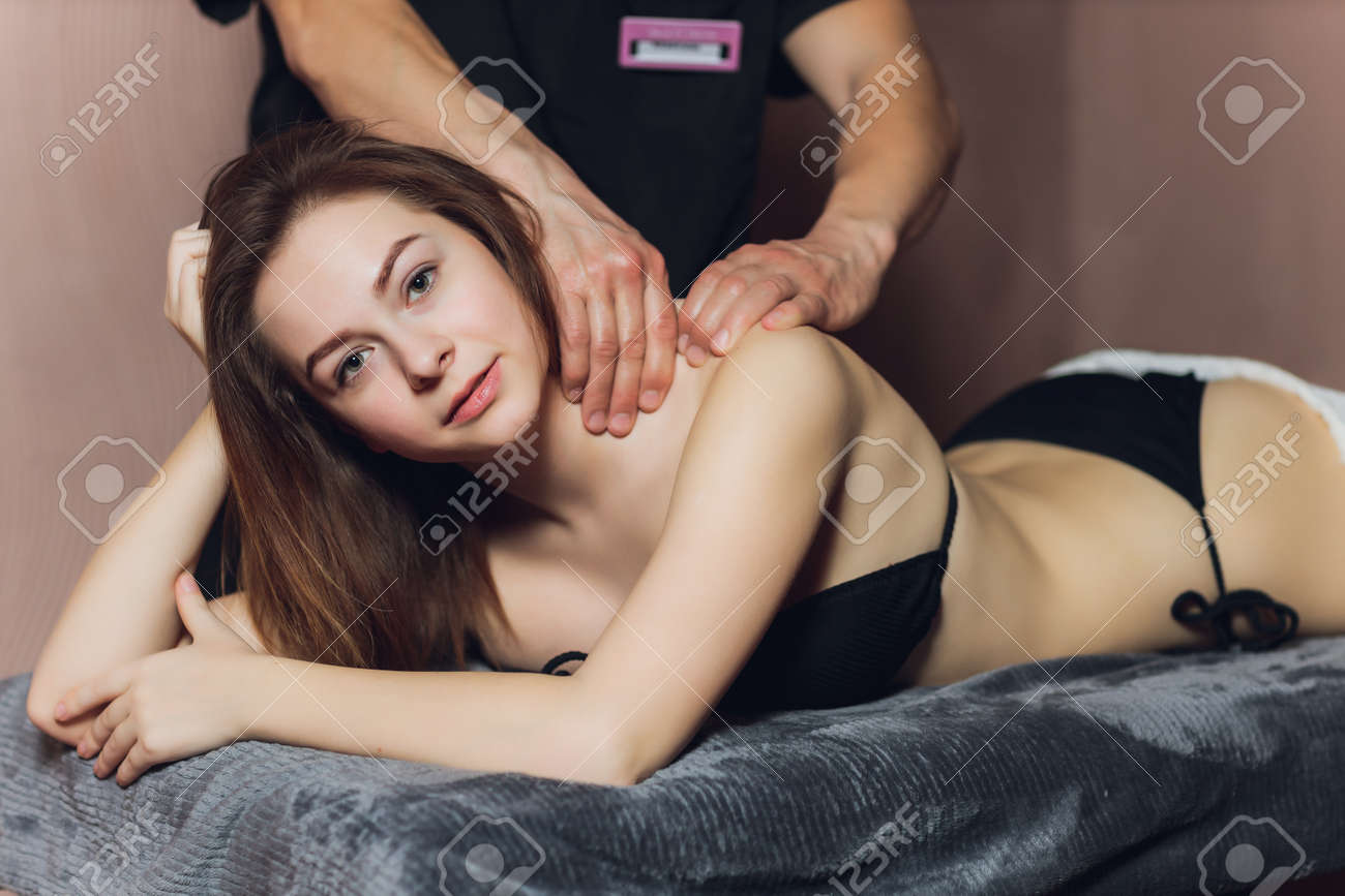 An attractive caucasian woman lying down on a massage bed at a spa. - 167226327