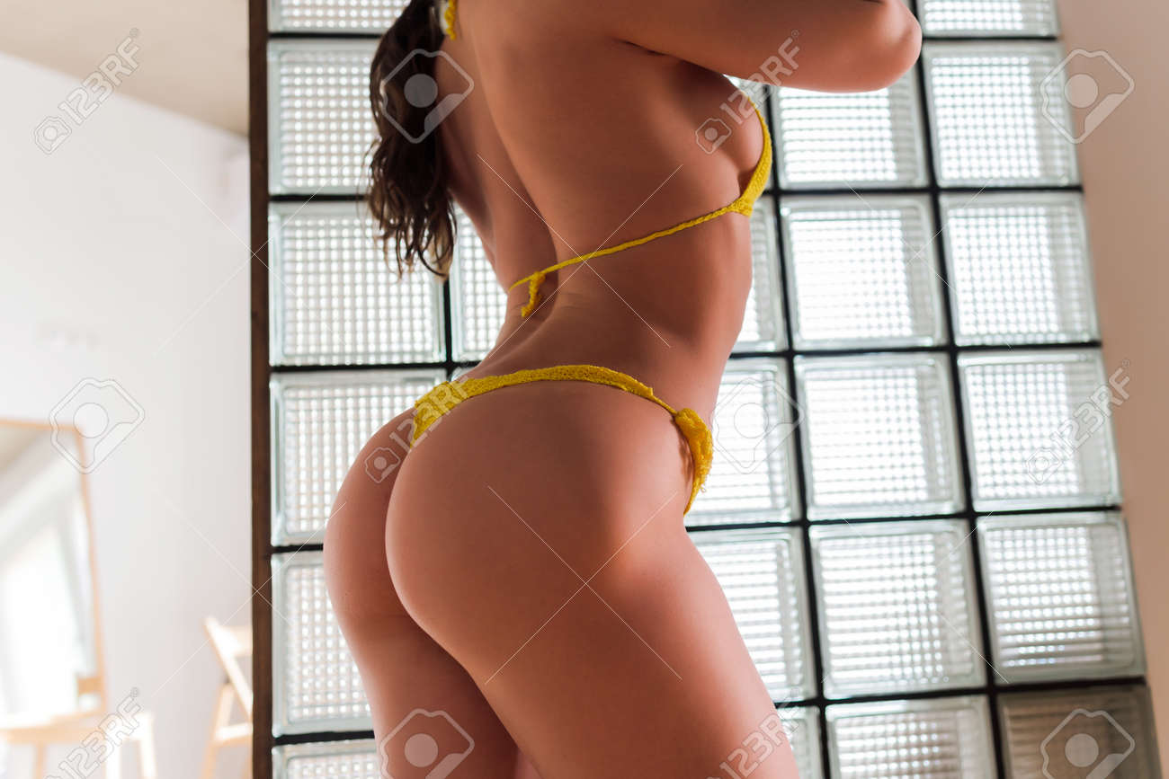 Extremely beautiful and young adult caucasian woman wearing lingerie in a boudoir bedroom setting in various poses. - 169523449