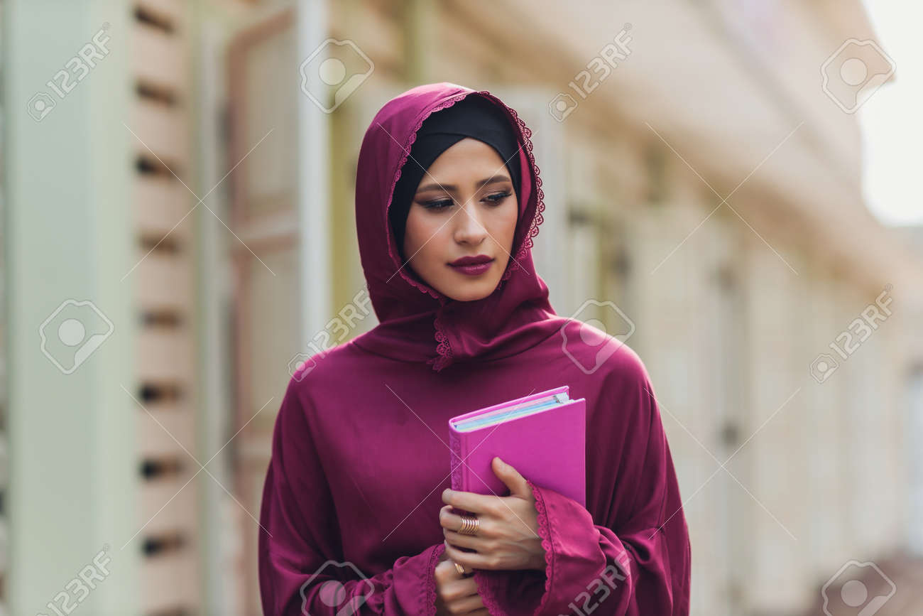 Confident Arab businessman smiling and walks of Dubai. Arab Business vumen hijab is in the streets against the skyscrapers of Dubai. The woman is dressed in a black abaya. - 169483460