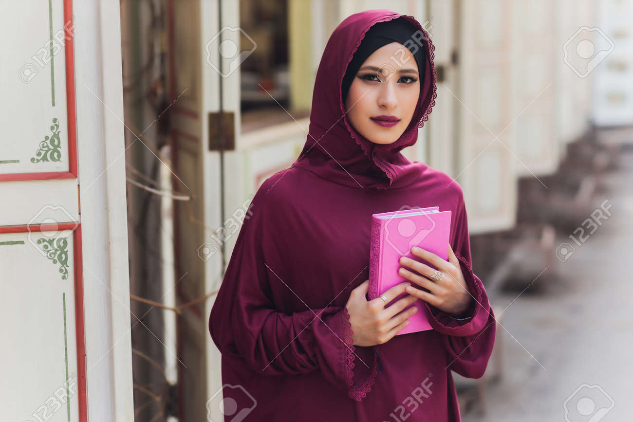 Confident Arab businessman smiling and walks of Dubai. Arab Business vumen hijab is in the streets against the skyscrapers of Dubai. The woman is dressed in a black abaya. - 169483466