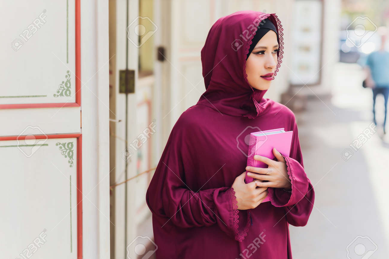 Confident Arab businessman smiling and walks of Dubai. Arab Business vumen hijab is in the streets against the skyscrapers of Dubai. The woman is dressed in a black abaya. - 169483467