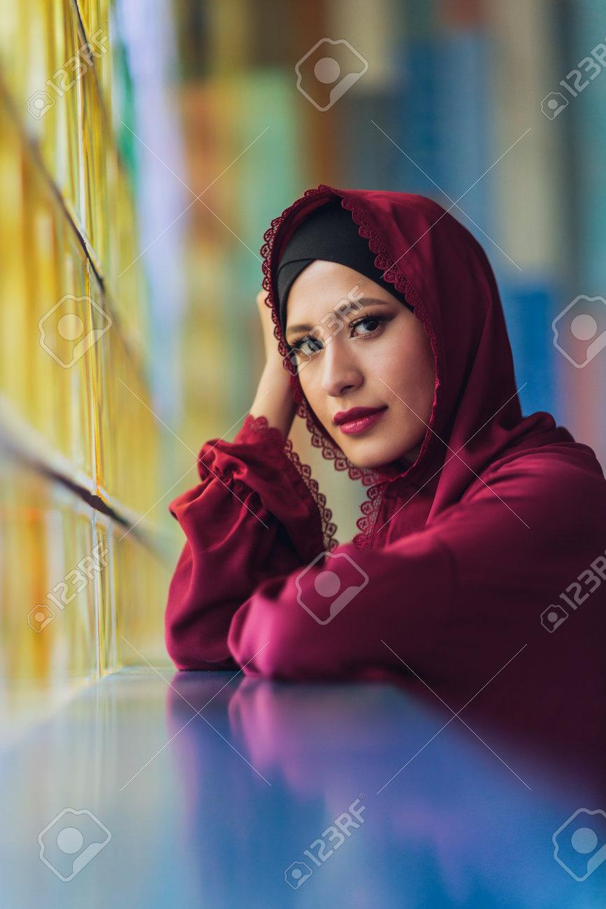 Arabian young muslim woman sitting in a cafe. - 169483479