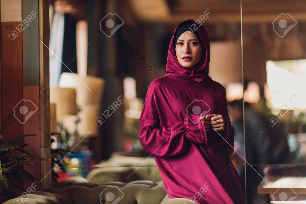Arabian young muslim woman sitting in a cafe. - 169483497