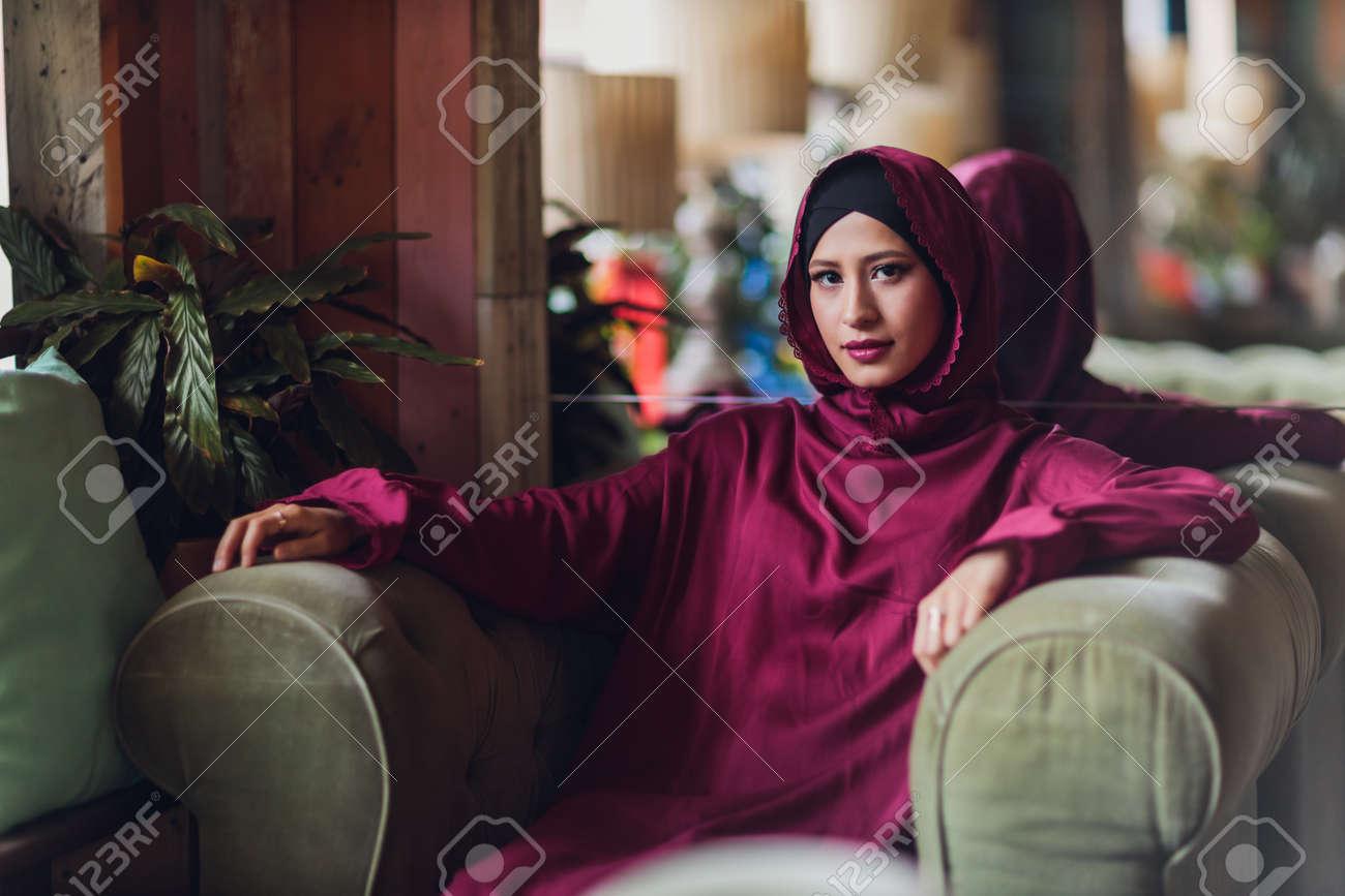 Arabian young muslim woman sitting in a cafe. - 169483501