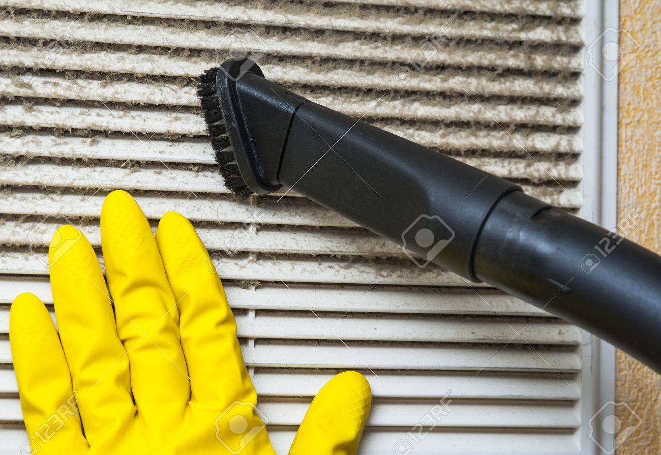 Hand in yellow glove and vacuum cleaner pipe. Ventilation grill cleaning. - 55594410
