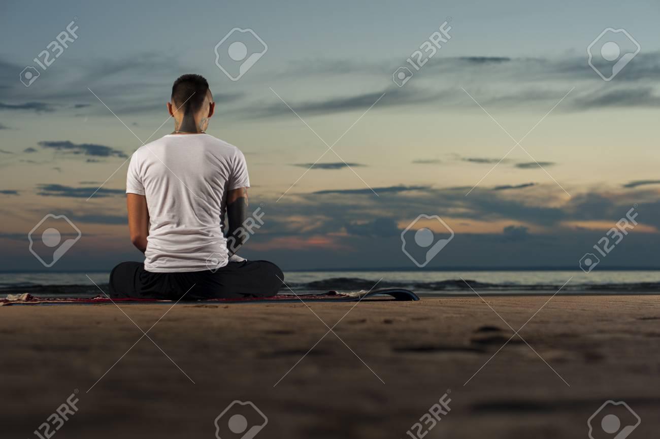Jeune Homme Tatouage Meditant Sur La Plage Au Coucher Du Soleil