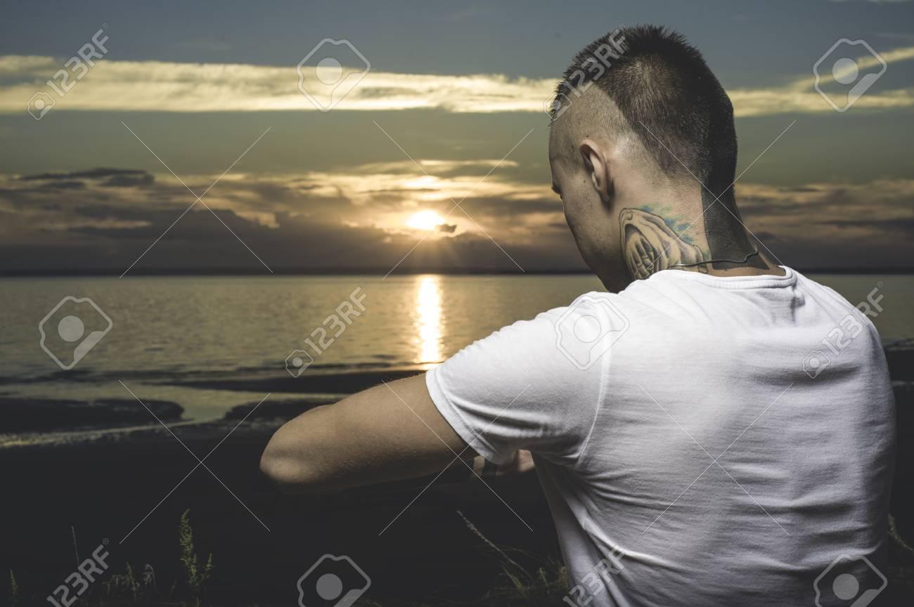 Hombre Joven Del Tatuaje Que Practica Yoga En La Playa En La Puesta