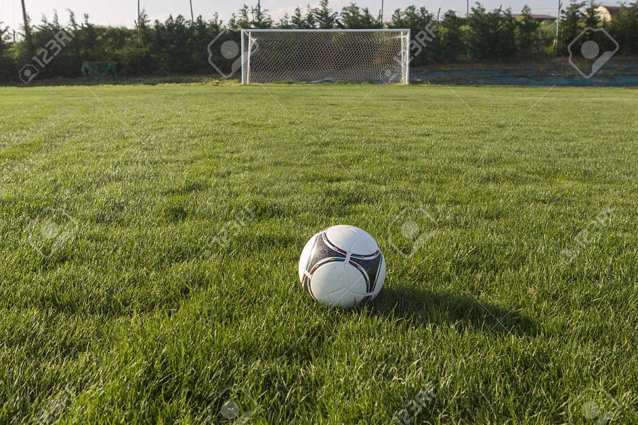 0a45d0acc Soccer Ball In Goal Net With Green Grass Field Stock Photo, Picture ...