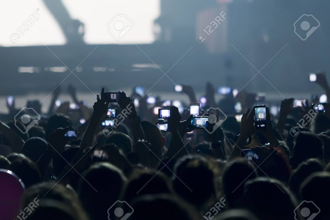 People taking photographs with touch smart phone during a music entertainment public concert Standard-Bild - 28230619