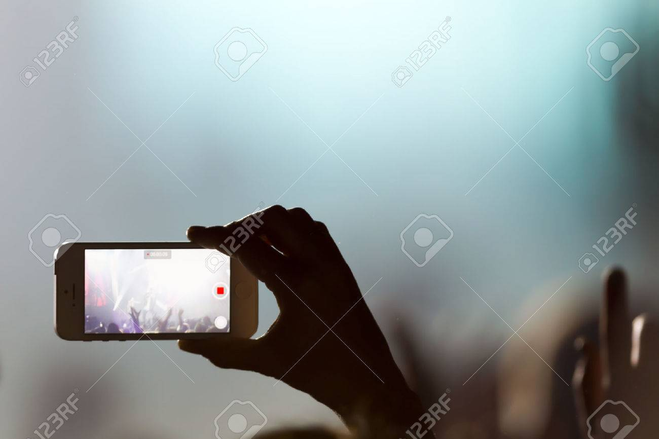People taking photographs with touch smart phone during a music entertainment public concert Standard-Bild - 28268252