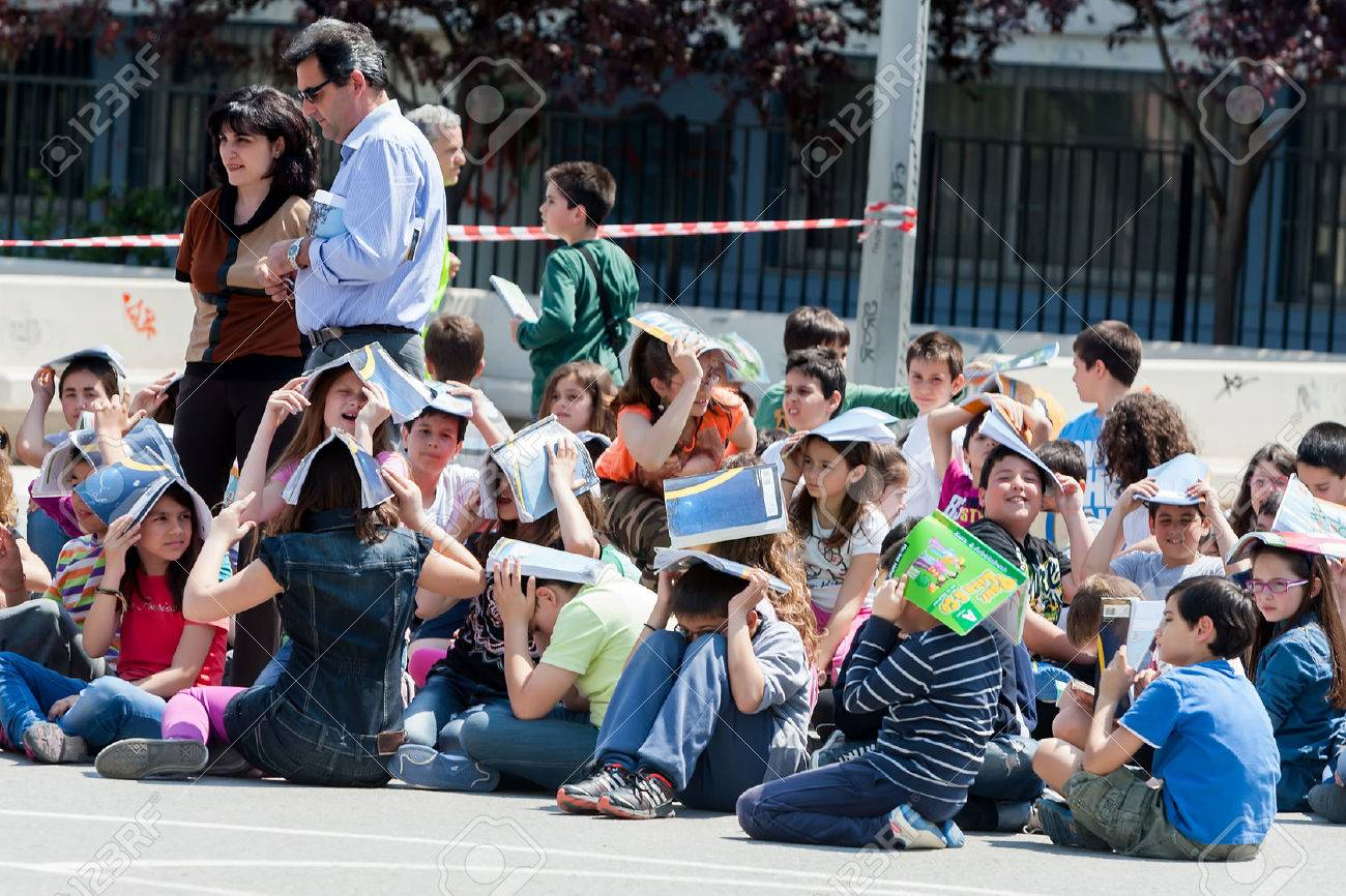 THESSALONIKI, GREECE- APRIL 24, 2013: Children sitting at the school yard, protecting their heads with books. Earthquake exercise, drill. 6th primary school in Thessaloniki, Greece. Standard-Bild - 30000134