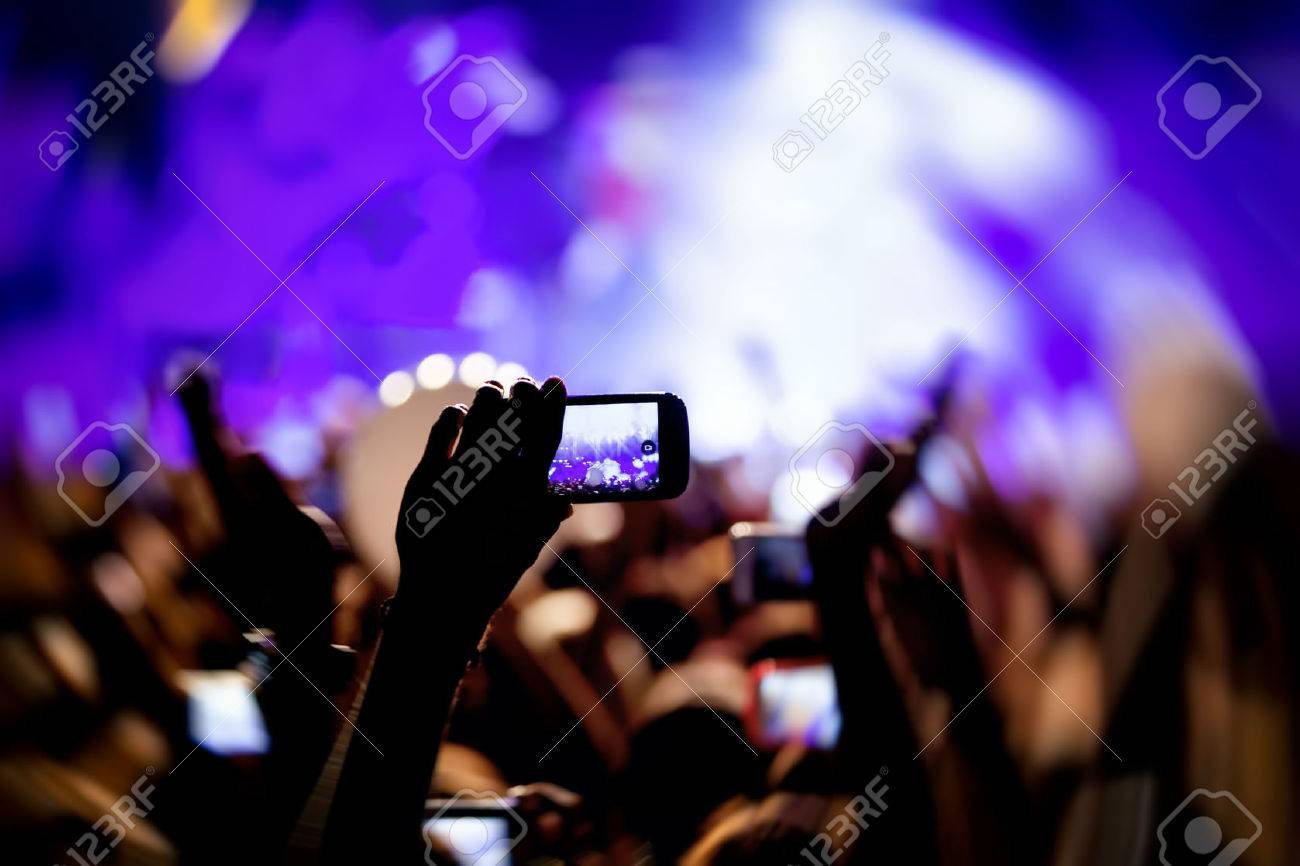 People taking photographs with touch smart phone during a music entertainment public concert Standard-Bild - 33079032