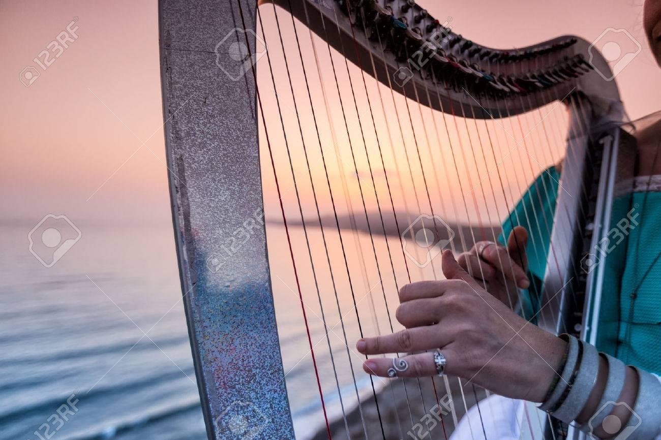 Nahaufnahme von den Händen der Frau spielt Harfe durch das Meer bei Sonnenuntergang in Santorini, Griechenland Standard-Bild - 48308081