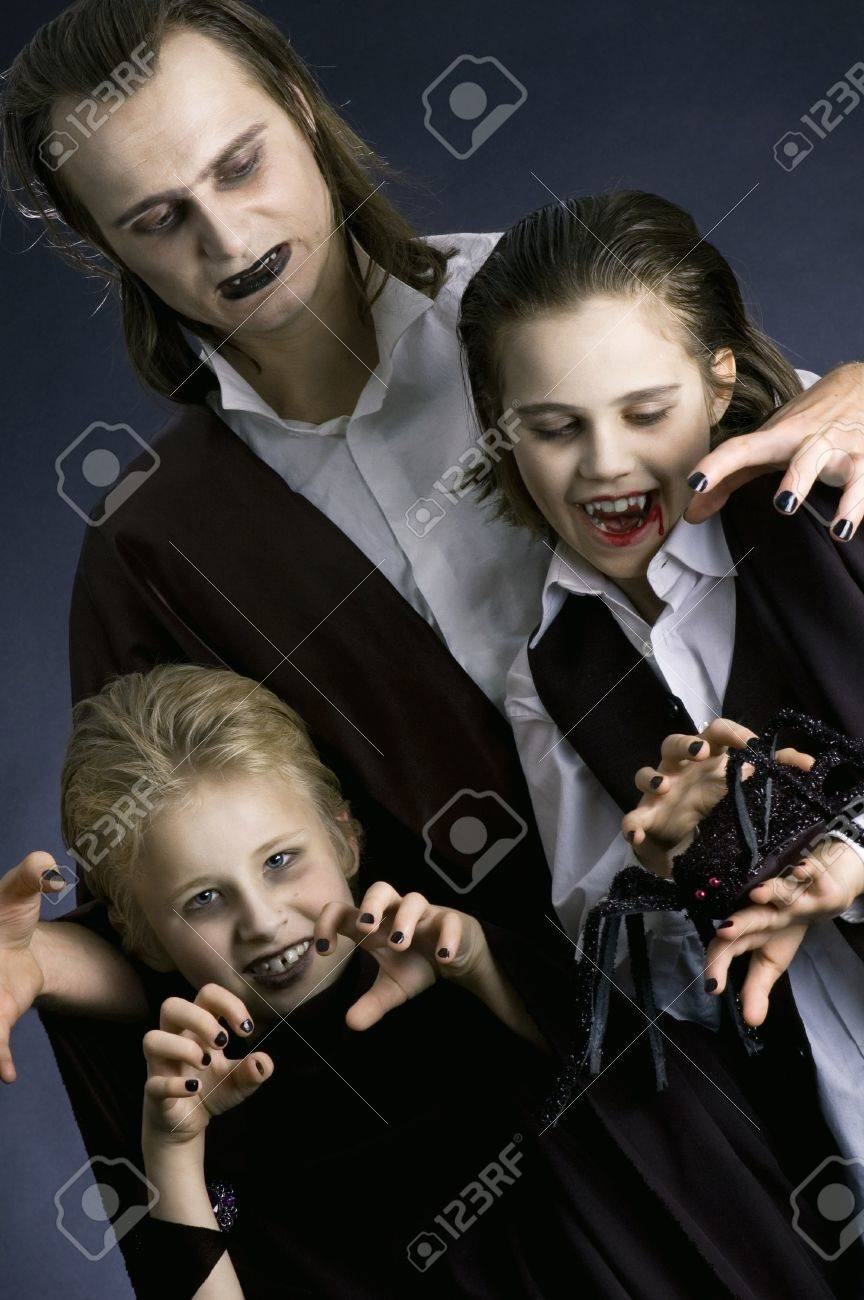 Father with children dressed up as vampires and making angry faces. Stock Photo - 10999350