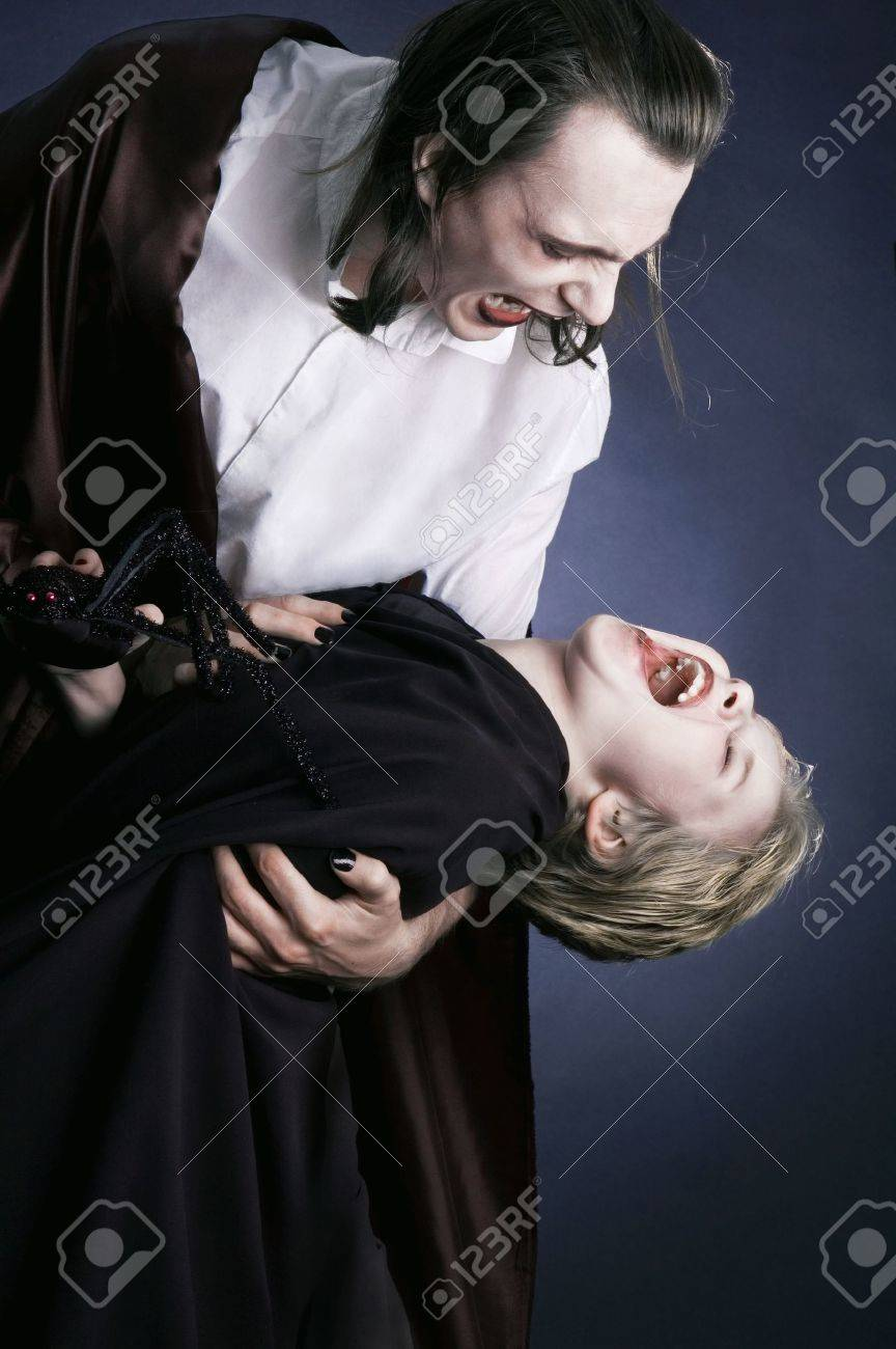 father and son playing vampire and victim dressed up in halloween