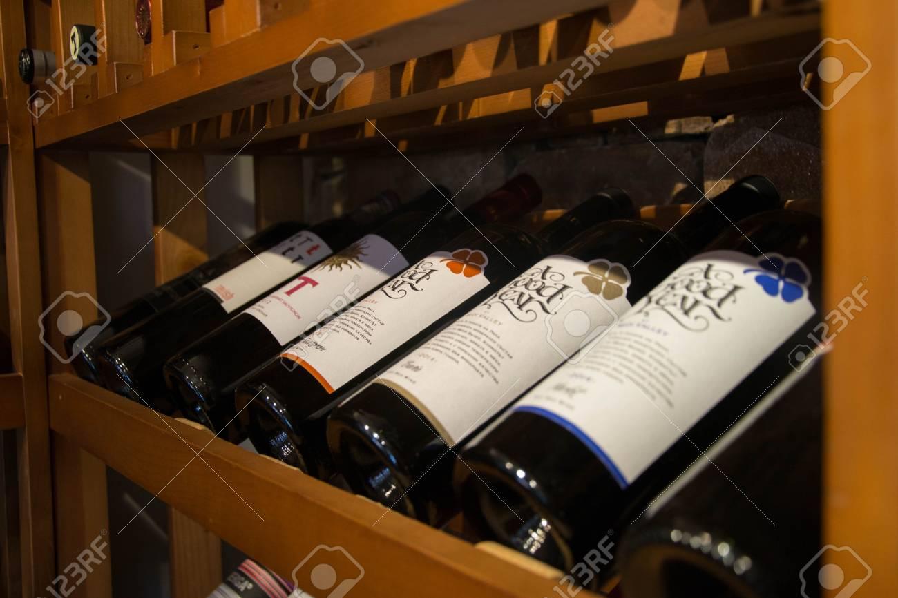 Bottles of wine in the cellar, restaurant, elite drinks on shelves with written names - 117481339