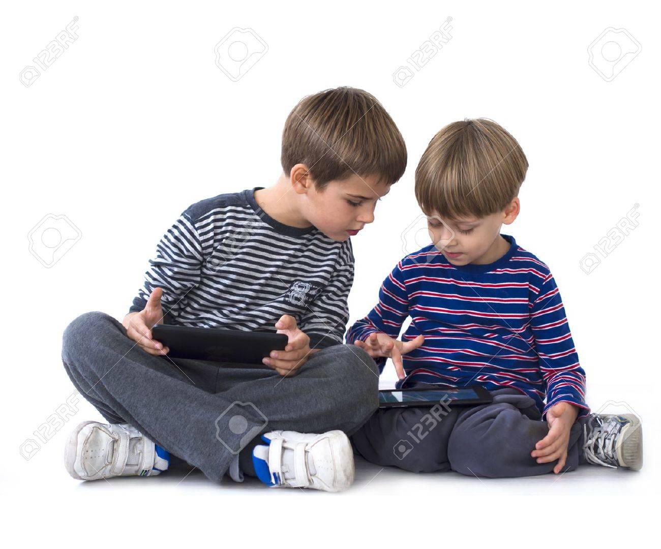 Brothers playing games on computer tablets Stock Photo - 18237371