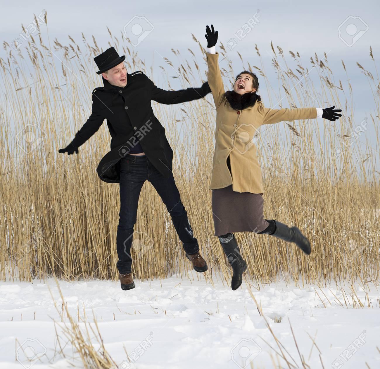Happy man and woman jump on lake beach Stock Photo - 17785488