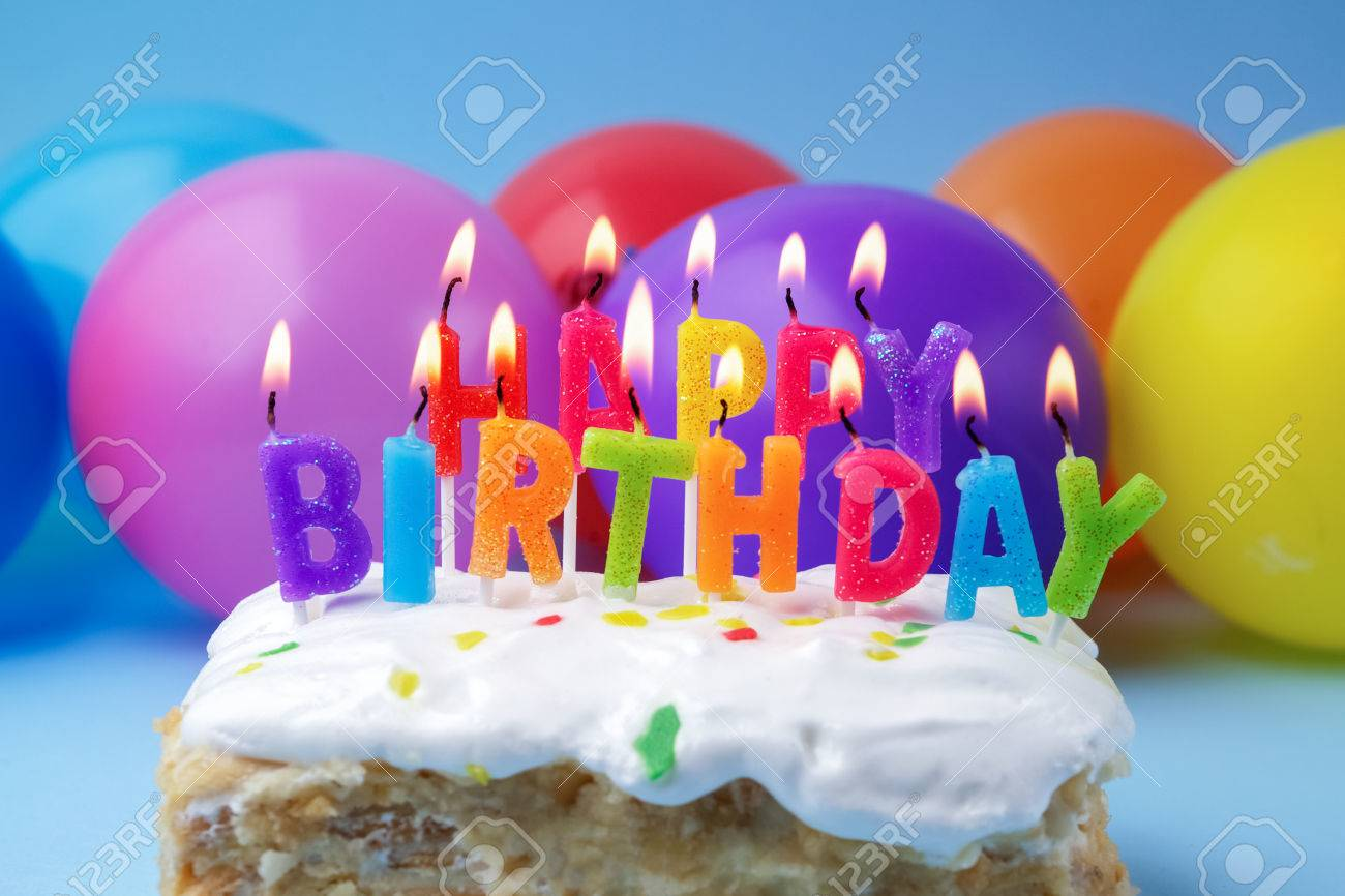 Cake With Birthday Greetings From Burning Candles On A Colored