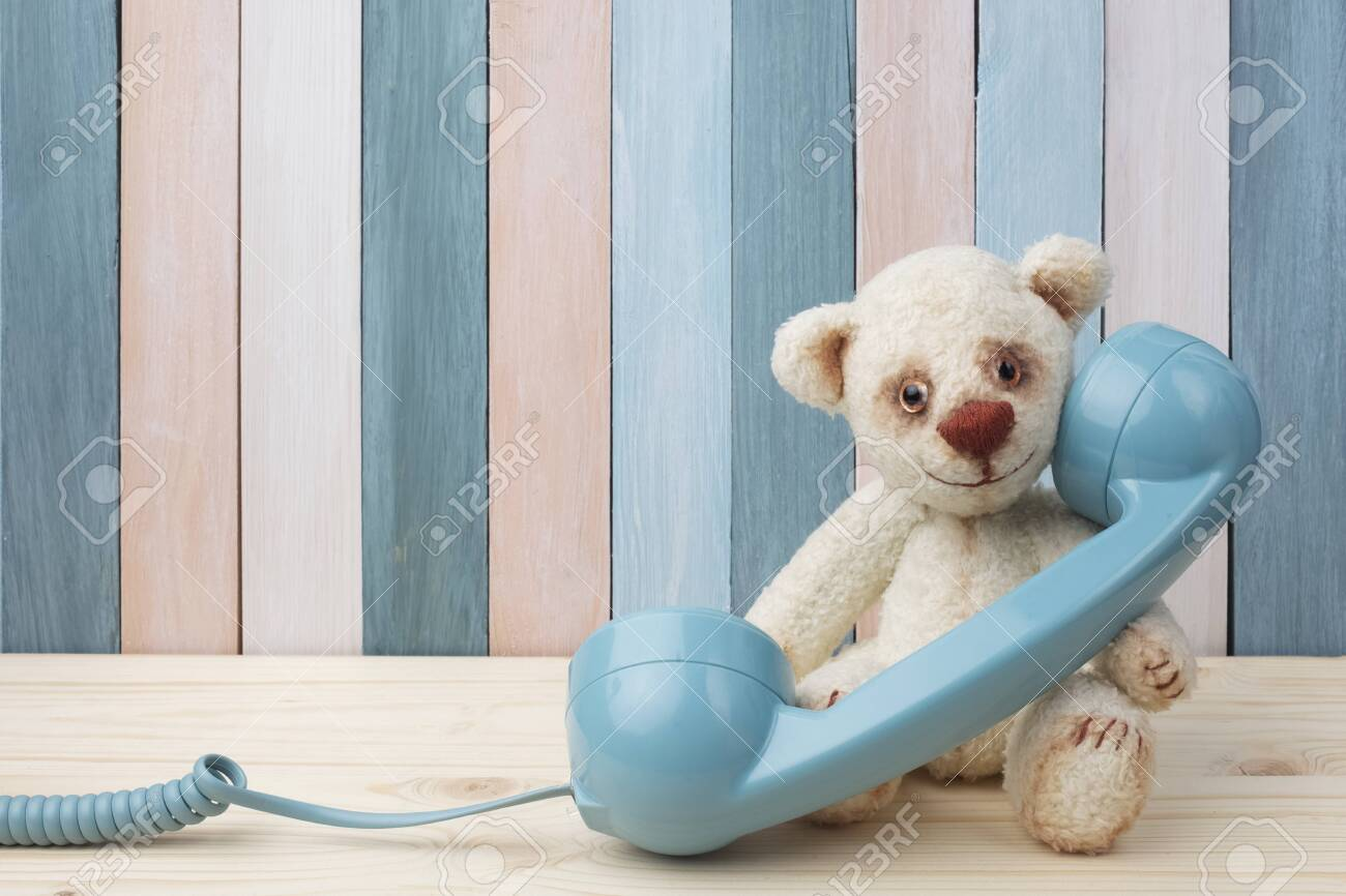 Vintage Teddy Bear with retro telephone on wooden background - 122222939