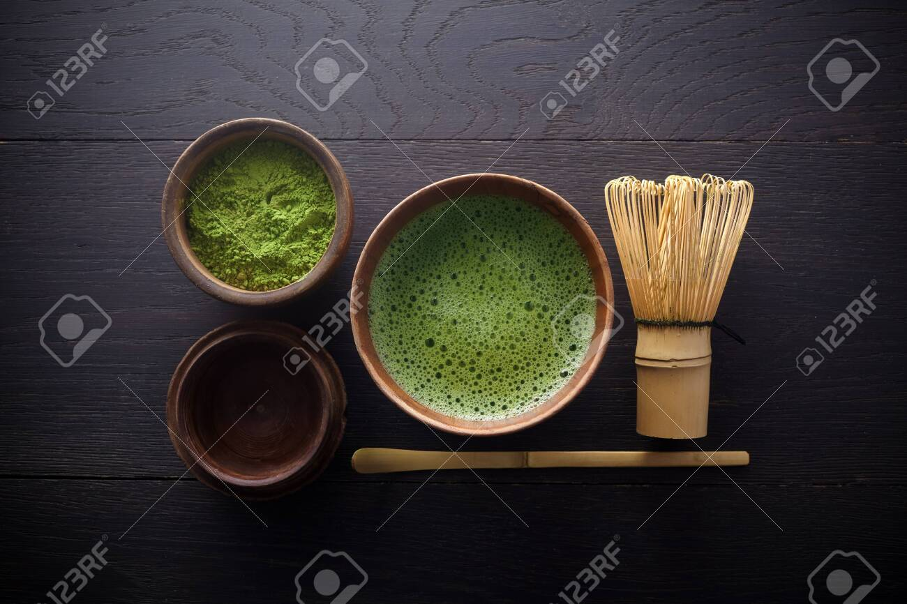 Matcha powder. Organic green matcha tea ceremony. Healthy drink. Traditional japanese drink on black wooden background - 143211237