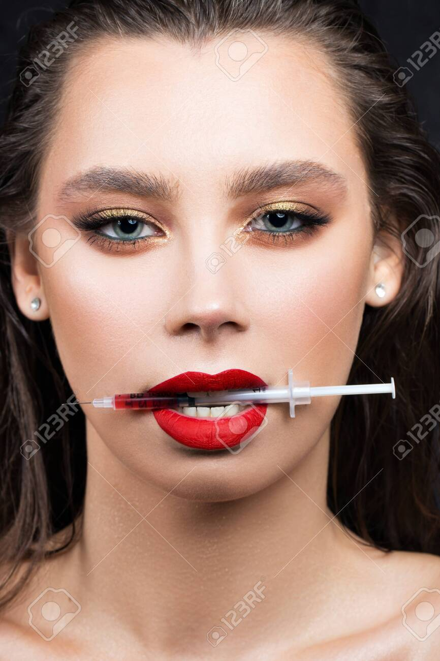 Portrait of a girl with a syringe for lip injections filled with
