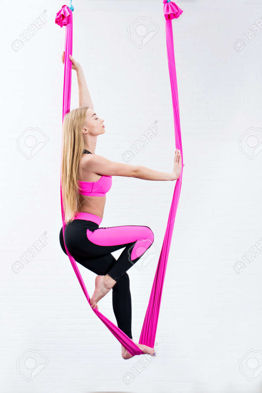 beautiful young girl antigravity yoga on a pink silk hammock while doing. - 170929818