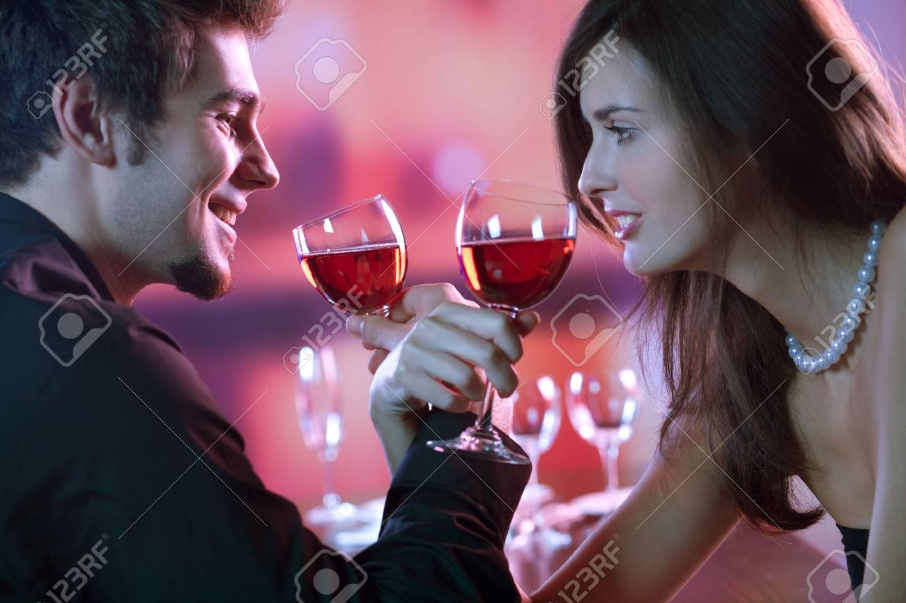 Young couple sharing a glass of red wine in restaurant, celebrating or on romantic date Stock Photo - 891359