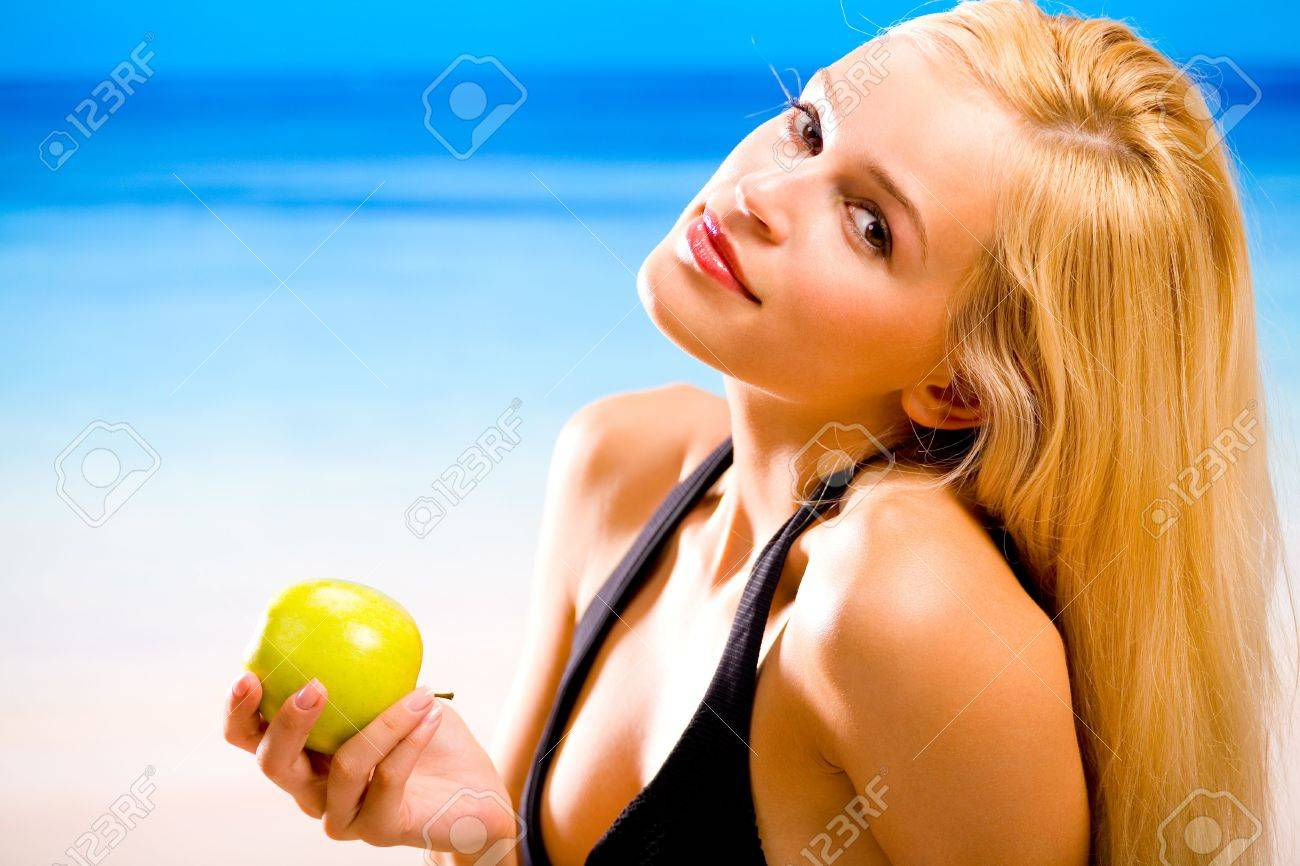 Young beautiful woman with apple in bikini at beach Stock Photo - 1000834