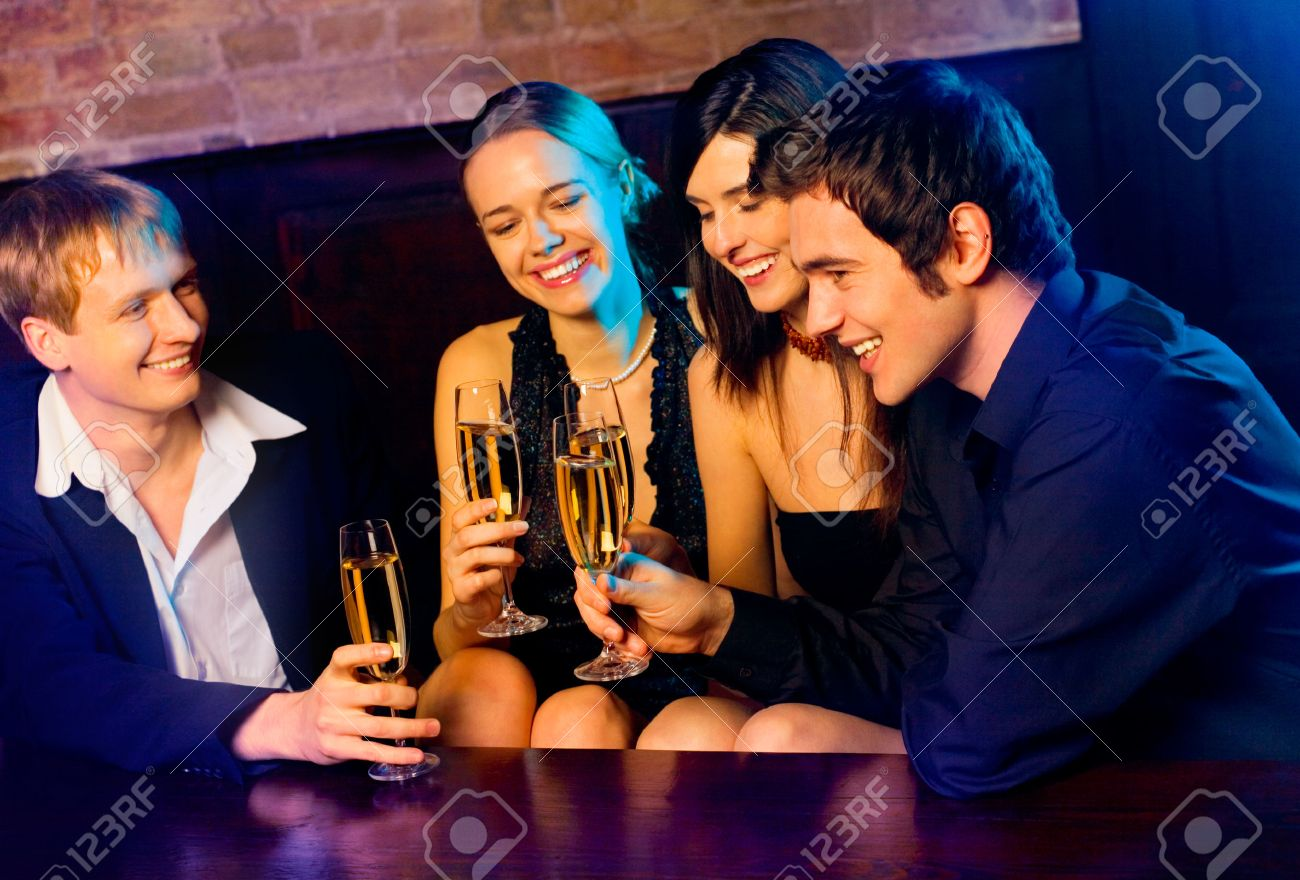 Two young happy smiling couples with champagne glasses at celebration, party or  date in night club Stock Photo - 1677042