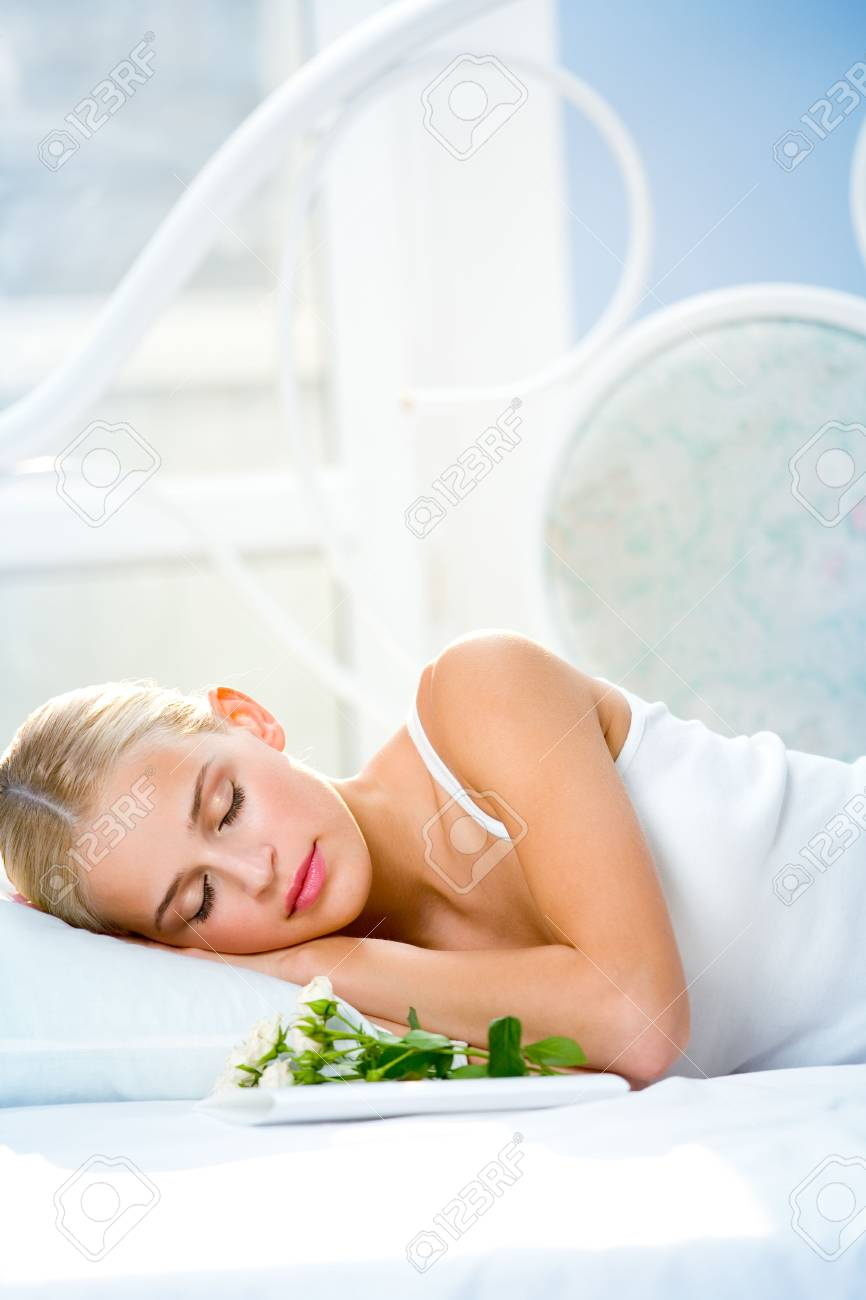 Portrait of young beautiful sleeping woman with gifts on bed at bedroom Stock Photo - 1834147