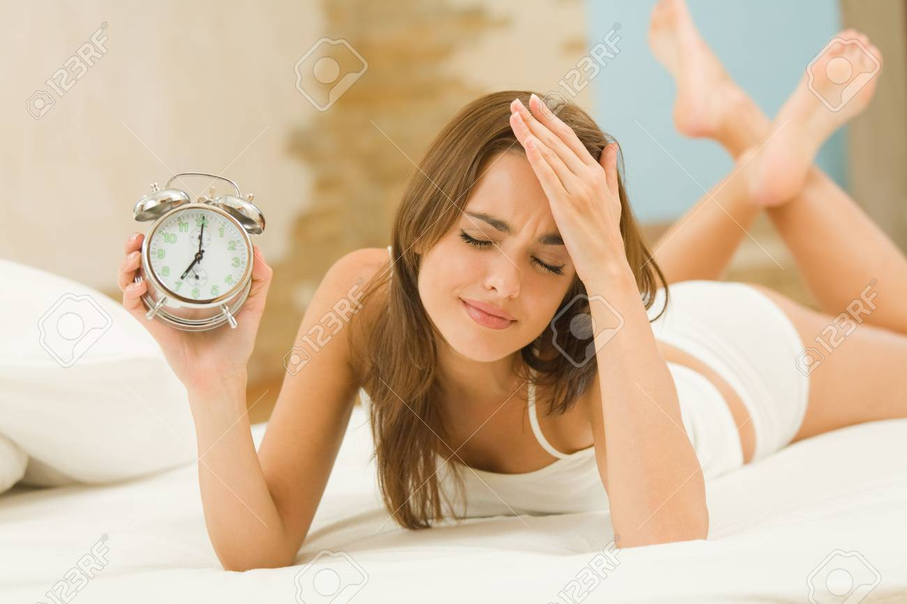 Young woman with alarmclock on the bed at the morning Stock Photo - 3384460