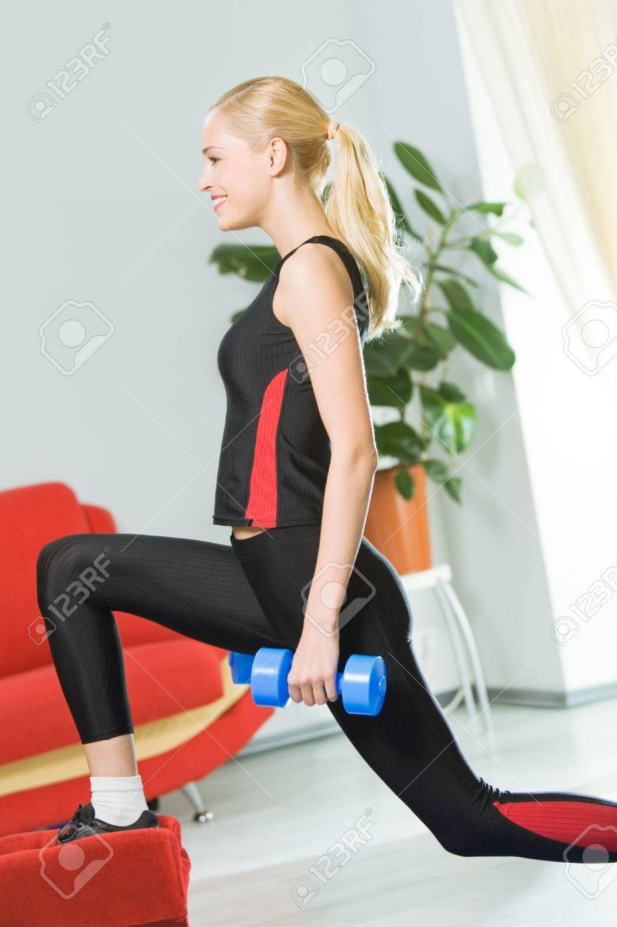 Young happy woman doing exercises with dumbbells at home Stock Photo - 5028586