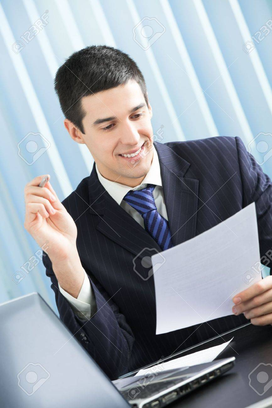 Happy businessman reading document at office Stock Photo - 5069777