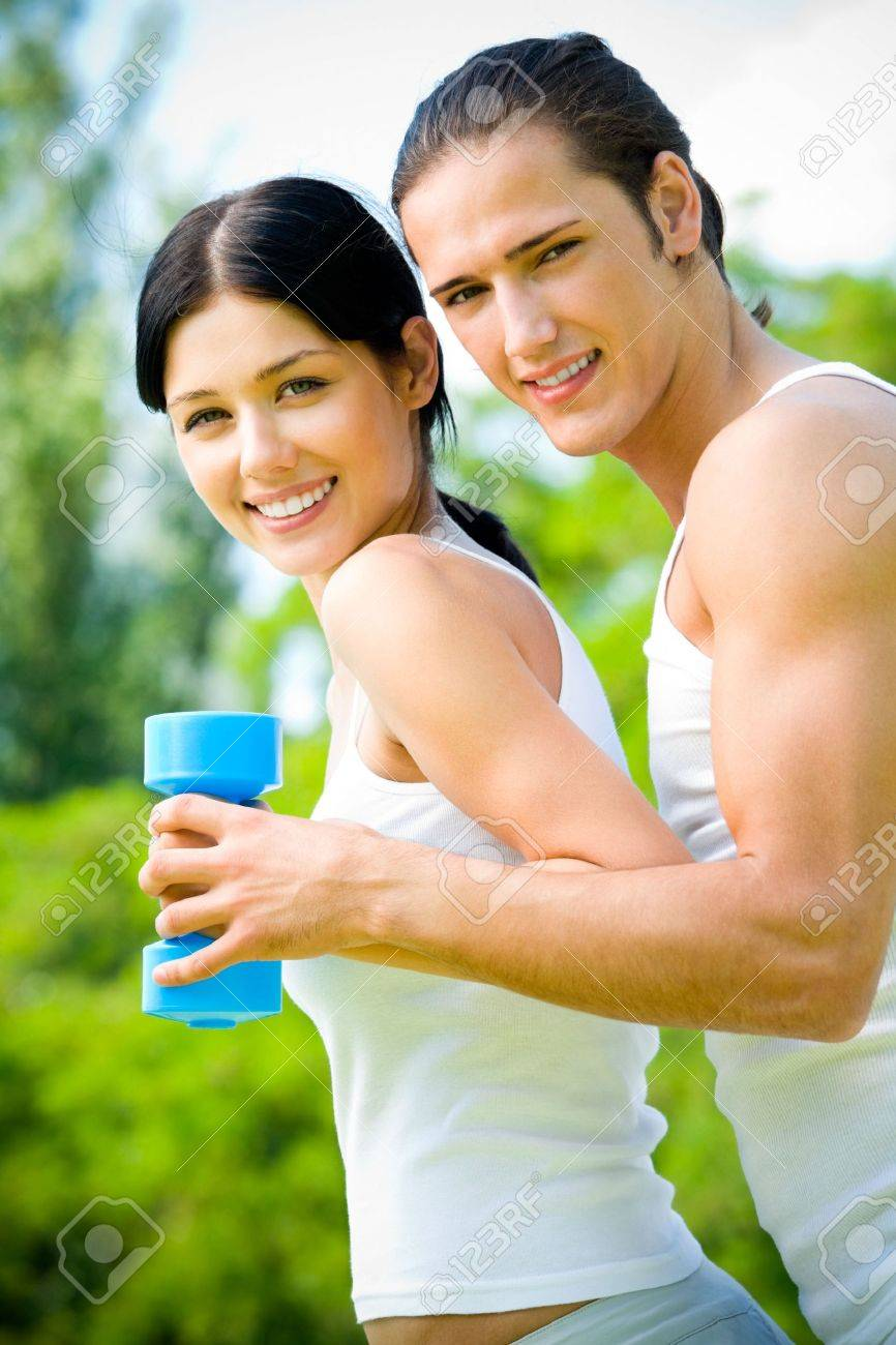 Young happy couple exercising with dumbbell, outdoors Stock Photo - 6783497