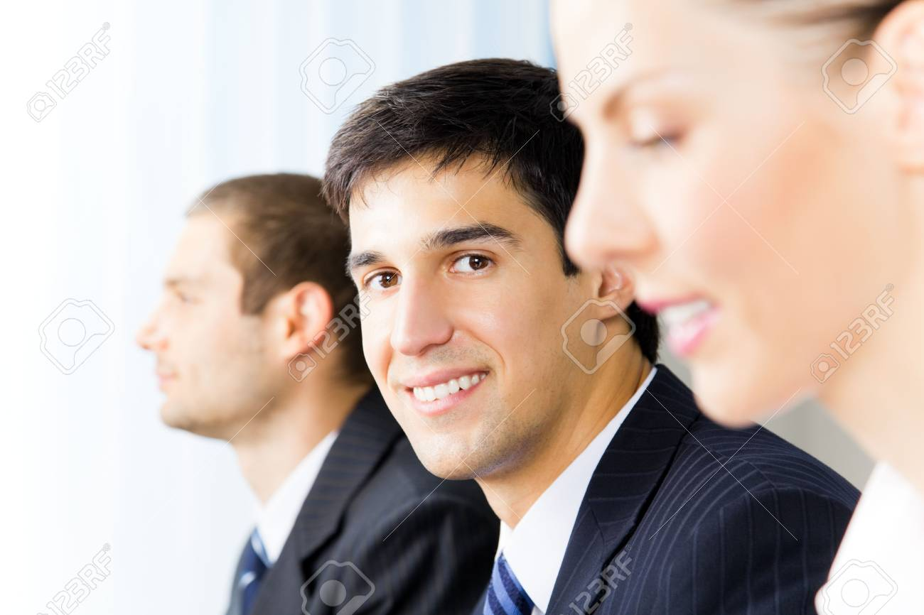 Three young successful businesspeople at office, with selective focus on man Stock Photo - 7875268