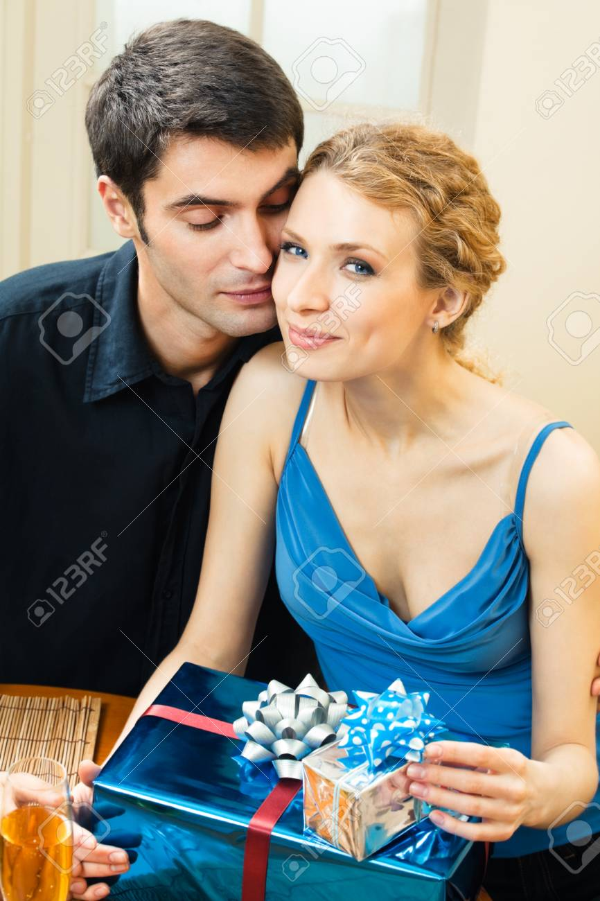 Young happy smiling amorous couple with gift and champagne at home Stock Photo - 8697475