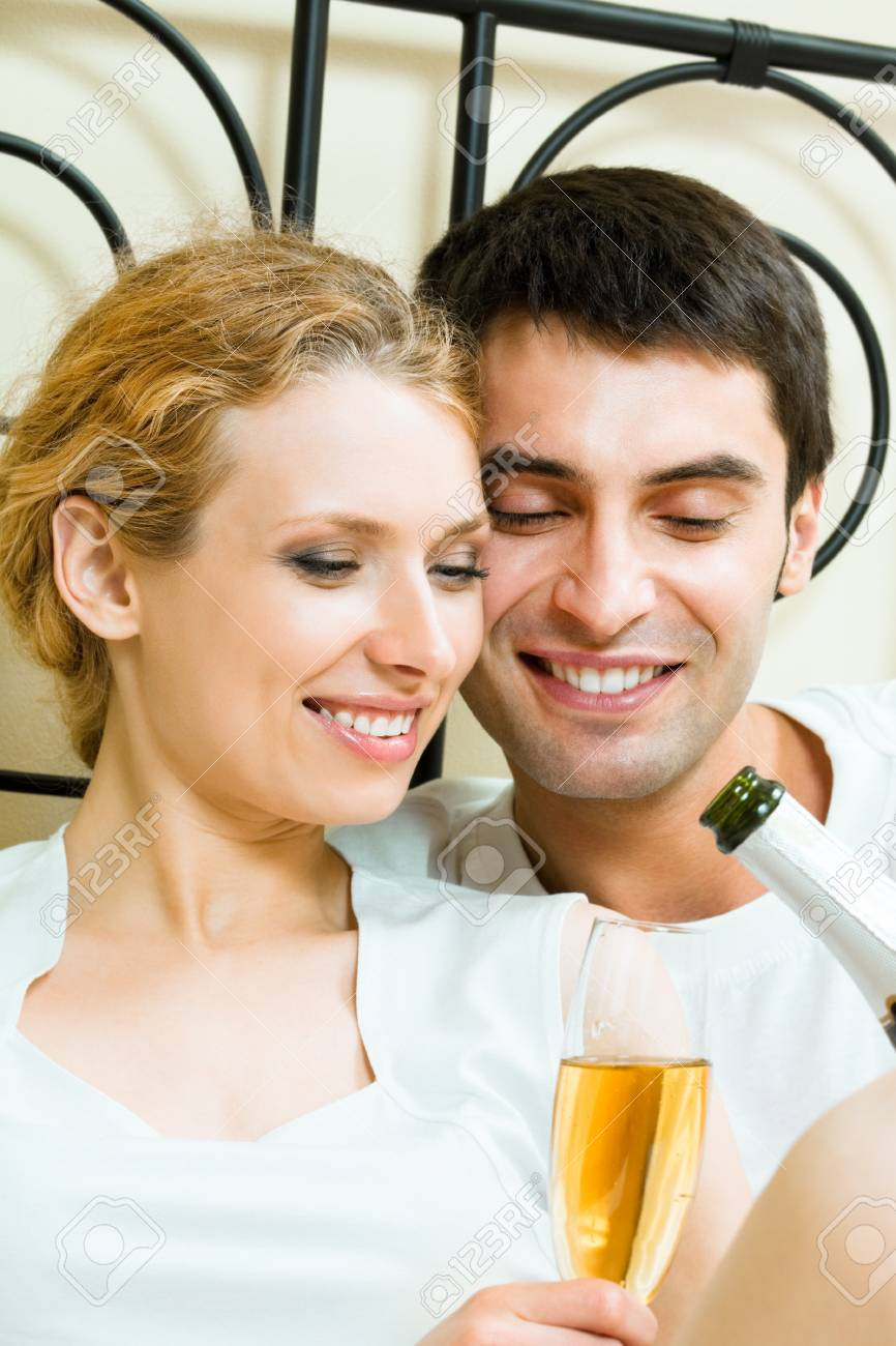 Young happy amorous couple celebrating with champagne at bedroom Stock Photo - 8697465