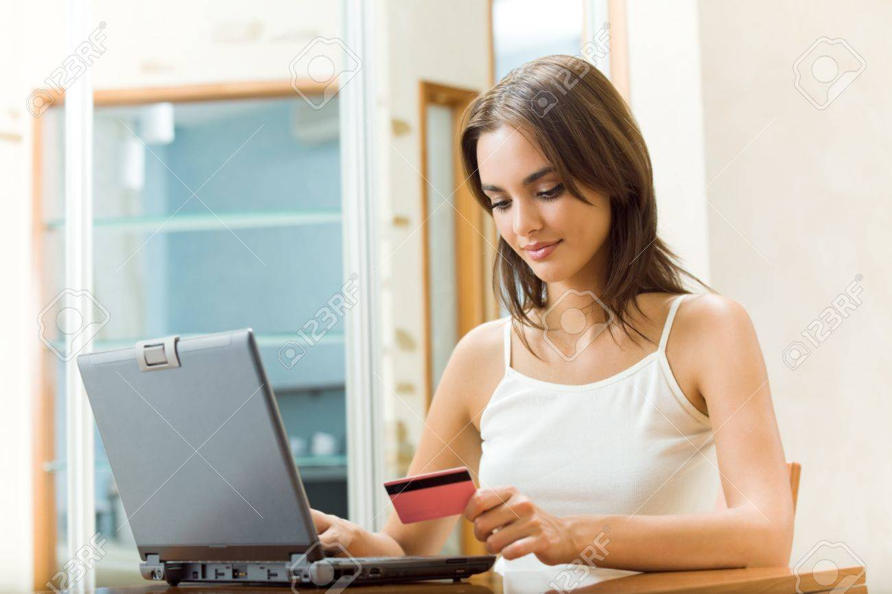Young happy smiling woman paying by plastic card, at home Stock Photo - 8697479