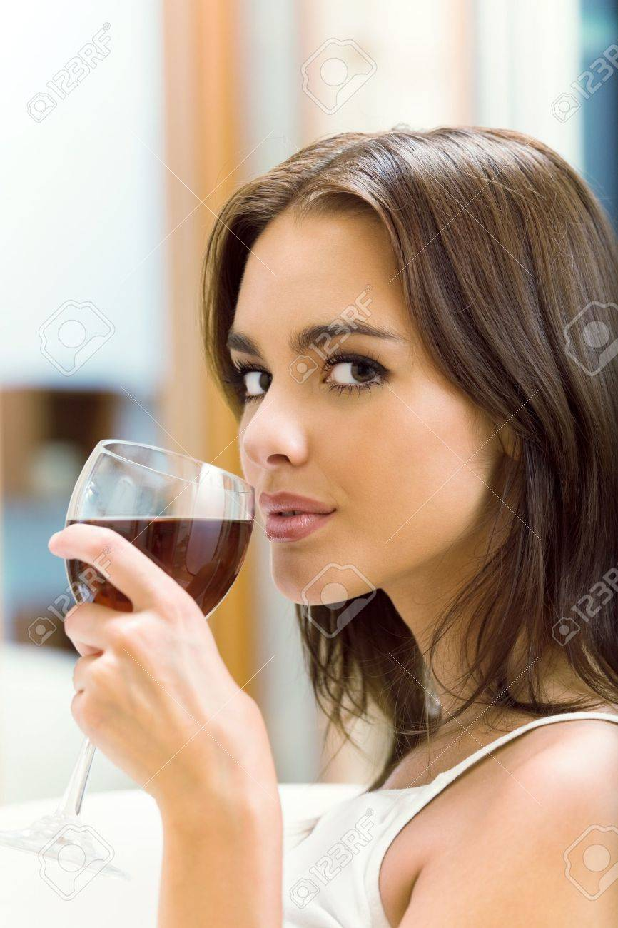 Portrait of young woman with glass of red wine, at home Stock Photo - 8697576