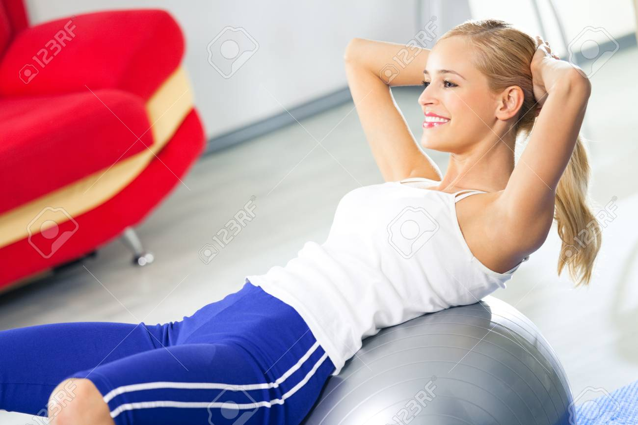 Young happy smiling woman in sportswear, doing fitness exercise with fit ball, indoors Stock Photo - 8876451