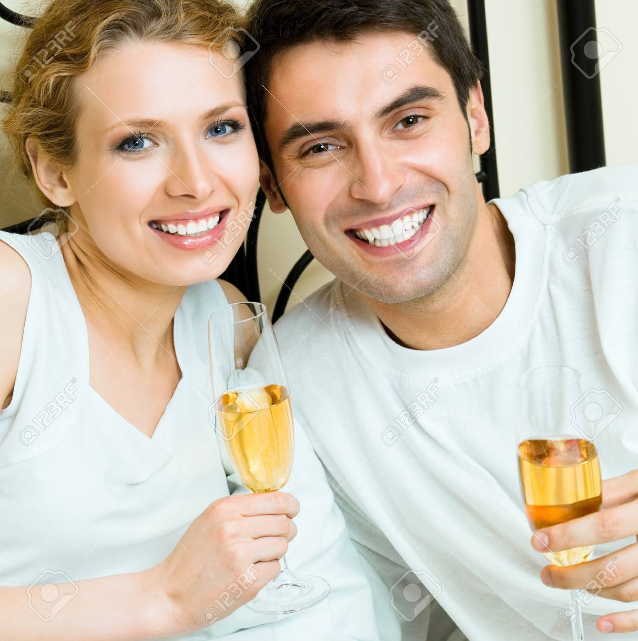 Young happy smiling amorous couple celebrating with champagne at bedroom Stock Photo - 9896069