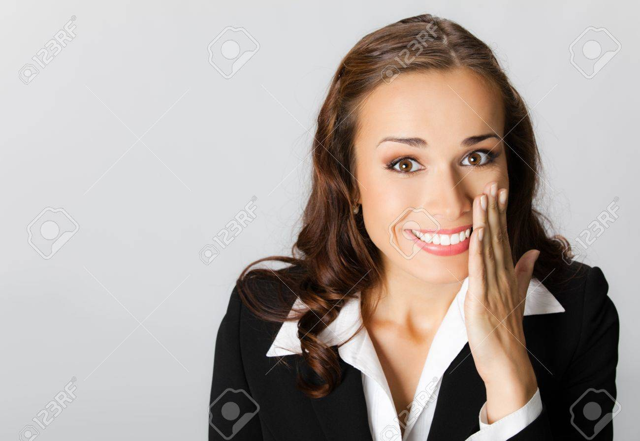 Portrait of happy smiling young business woman covering with hand her mouth, over grey background Stock Photo - 10549081