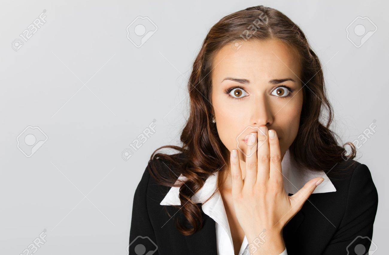 Portrait of surprised excited young business woman covering with hands her mouth, over grey background Stock Photo - 10548720